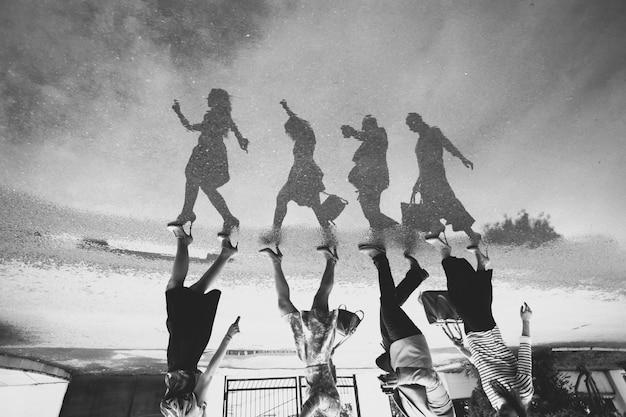 Weerspiegeling van een groep mensen in een plas op de weg. zwart en wit. Premium Foto
