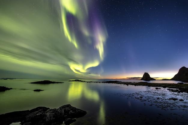 Weerspiegeling van het prachtige noorderlicht in de zee, omringd door heuvels in noorwegen Gratis Foto