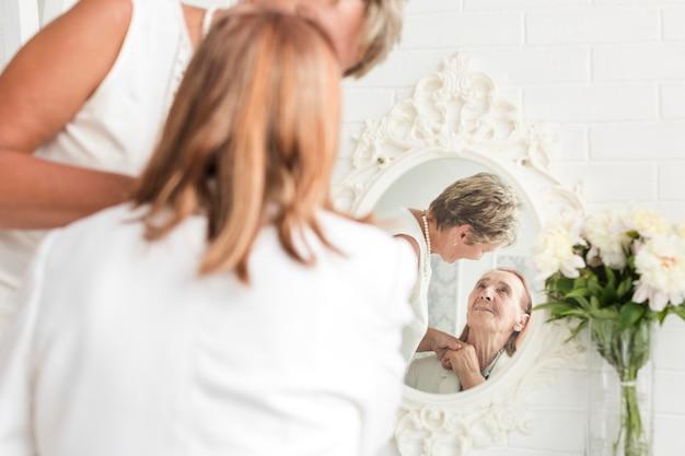 Weerspiegeling van moeder en dochter op spiegel thuis Gratis Foto