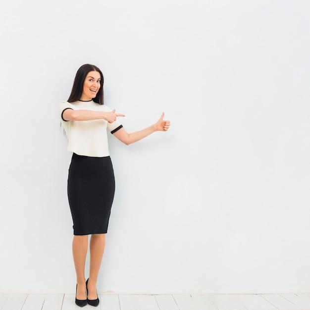 Weg wijzende vinger en vrouw die duim toont Gratis Foto