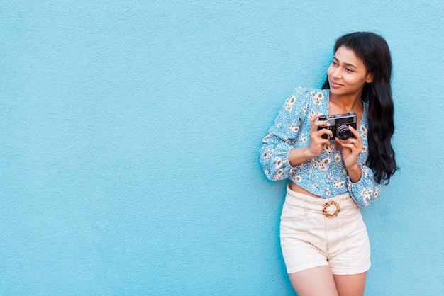 Wegkijkend vrouw en retro camera met exemplaarruimte Gratis Foto