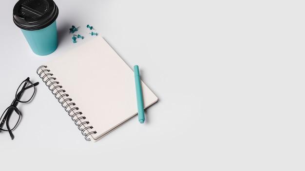 Wegwerp koffiekopje; pen; bril; spiraal blocnote en punaisespelden op witte achtergrond Gratis Foto
