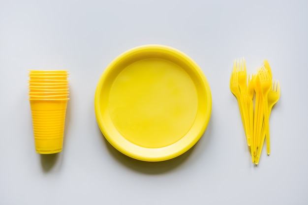 Wegwerp picknick gele gebruiksvoorwerpen, borden, kopjes, vorken op grijs. Premium Foto