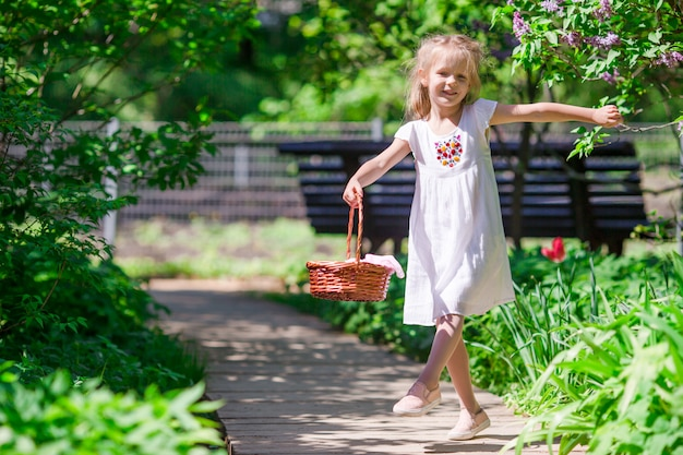 Weinig aanbiddelijk meisje met bloemen in tulpentuin Premium Foto