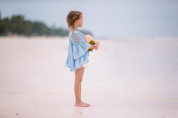 Weinig aanbiddelijk meisje met grote kokosnoot op wit zandstrand Premium Foto