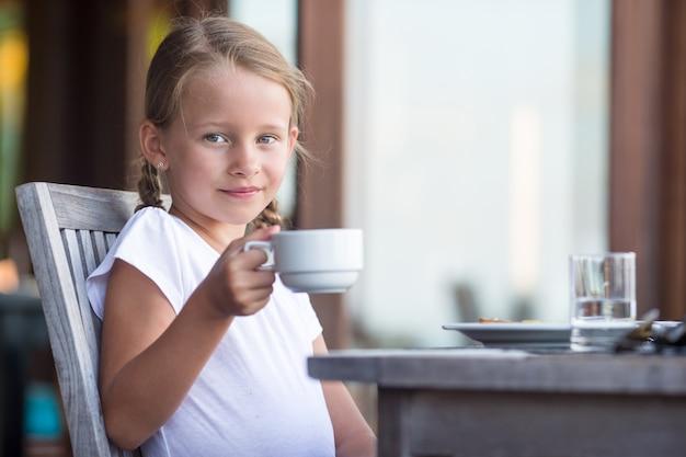 Weinig aanbiddelijke meisje het drinken thee op ontbijt in openluchtkoffie Premium Foto
