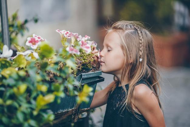 Weinig aanbiddelijke meisjeszitting dichtbij kleurrijke bloemen in de tuin Premium Foto