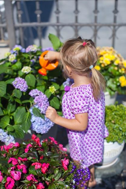 Weinig aardig meisje die bloemen met wateringcan water geven Premium Foto