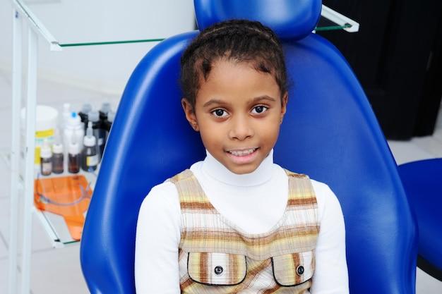 Weinig afrikaans meisje met donkere huid in tandheelkunde Premium Foto