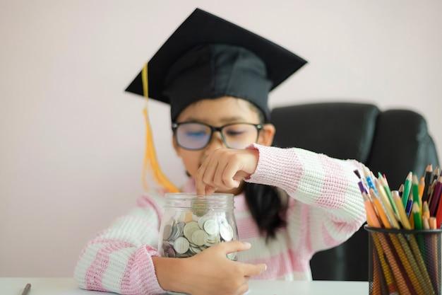Weinig aziatisch meisje dat gediplomeerde hoed draagt die duidelijke glaskruik koestert Premium Foto