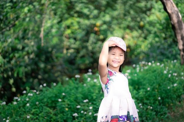 Weinig aziatisch meisje dat in kleding glimlacht terwijl het dragen van glb in het park Premium Foto