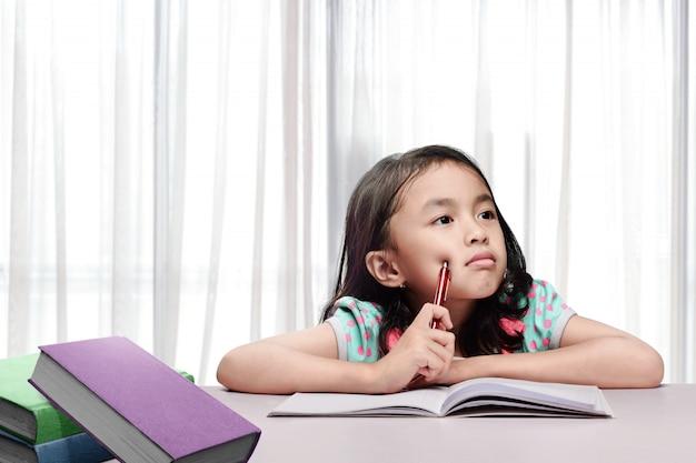 Weinig aziatisch meisje die met boek en pen denken wanneer het doen van thuiswerk Premium Foto