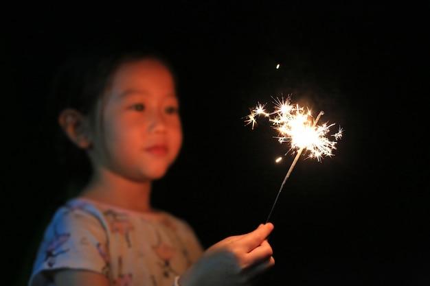 Weinig aziatisch meisje speelt vuur-sterretjes in het donker. Premium Foto