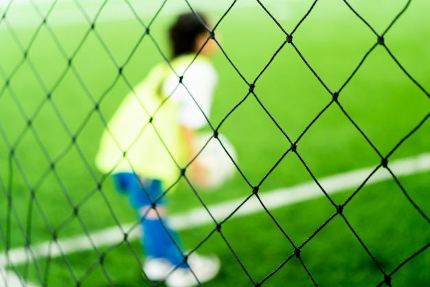 Weinig aziatisch meisje traint in overdekt voetbalveld wazig Premium Foto
