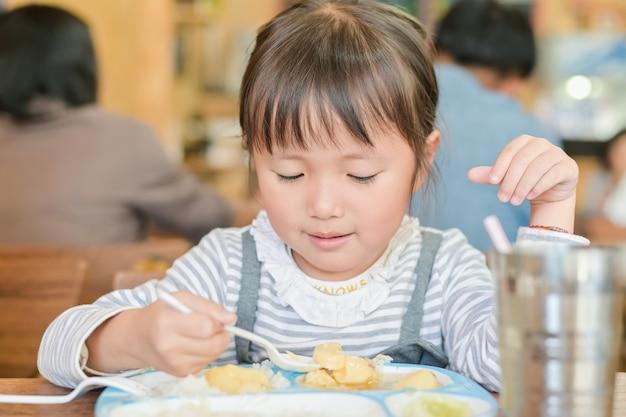 Weinig aziatische het gebruikslepel van het kindmeisje om voedsel op de te dineren lijst uit te scheppen. terwijl lunchen op tafel in restaurant Premium Foto