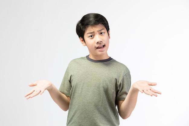 Weinig aziatische jongen met zwart haar in grappig acteren die aan het amuseren proberen. Premium Foto