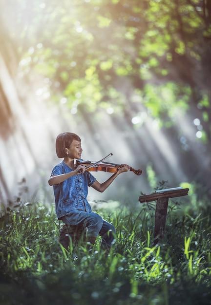 Weinig aziatische kind viool spelen in de open lucht Premium Foto