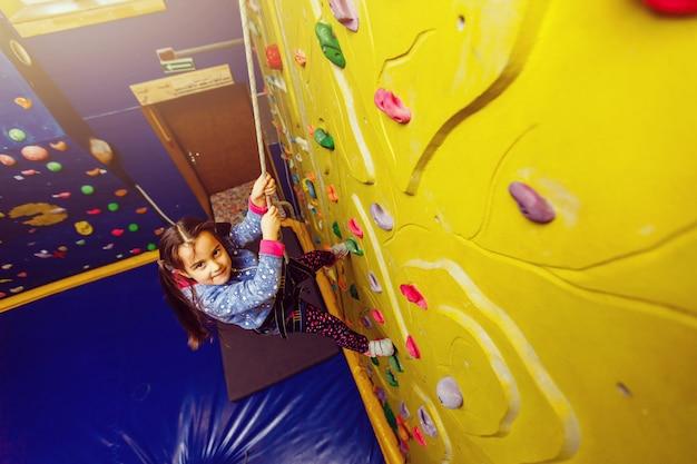 Weinig babymeisje met grappige hoort stijl beklimmende verticale muur en man die haar vastmaken van onderaan Premium Foto