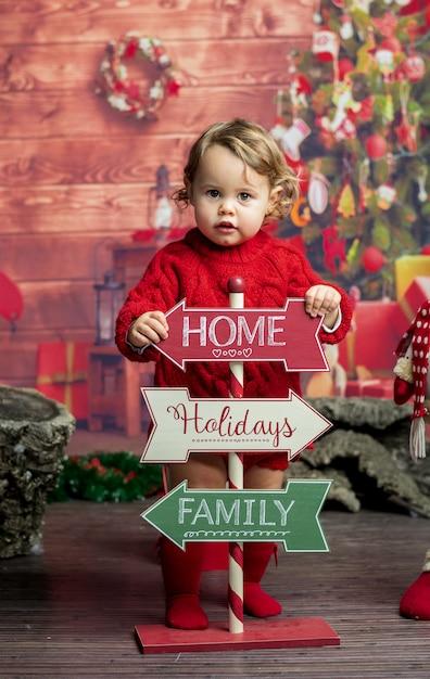Weinig blonde babymeisje met kerstmisuithangborden Premium Foto