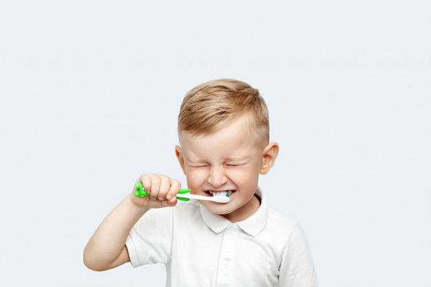 Weinig blonde jongen die zijn tanden in binnenlands bad leert poetsen Premium Foto
