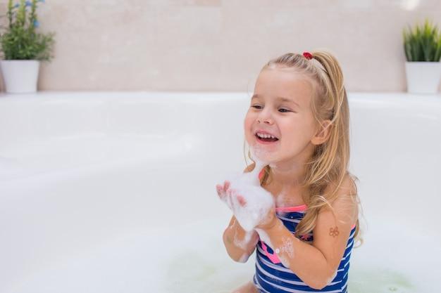 Weinig blondemeisje die schuimbad in mooie badkamers nemen. hygiëne van kinderen. shampoo, haarbehandeling en zeep voor kinderen. kinderen baden in groot bad. Premium Foto