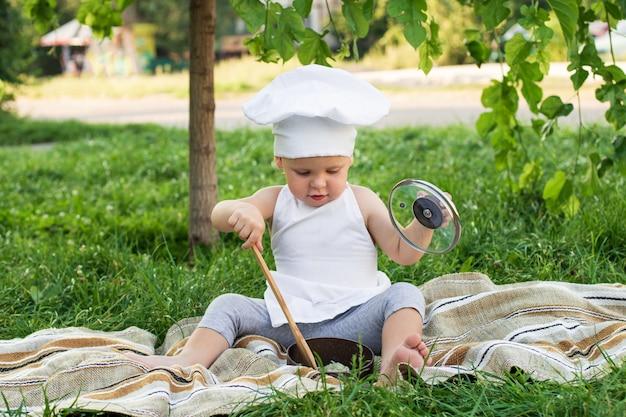 Weinig chef-kok kookt in openlucht deegwaren op een picknick. leuk kind in een kokkostuum met pan en kokende spatel op de groene aardmuur Premium Foto