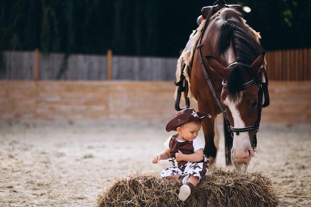 Weinig cowboy zittend op hooi Gratis Foto