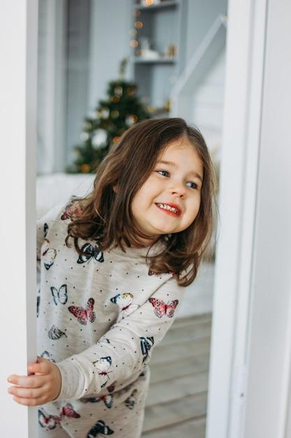 Weinig gelukkig donkerbruin meisje in comfortabele pyjama kijkt van de slaapkamer van het kinderenbed, kerstmistijd Premium Foto