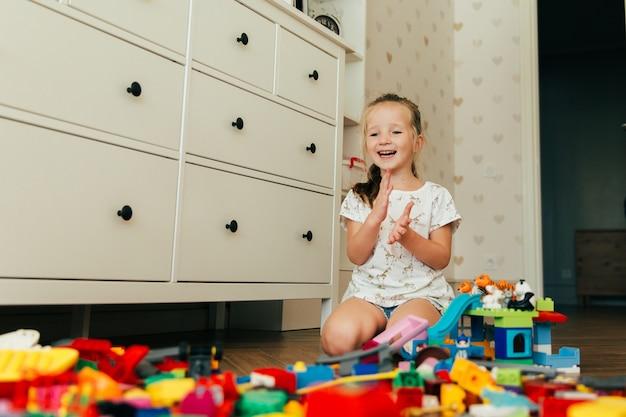 Weinig gelukkig meisje dat met kleurrijke stuk speelgoed blokken speelt. educatief en creatief speelgoed en spelletjes voor jonge kinderen. speeltijd en rommel in de kinderkamer Premium Foto