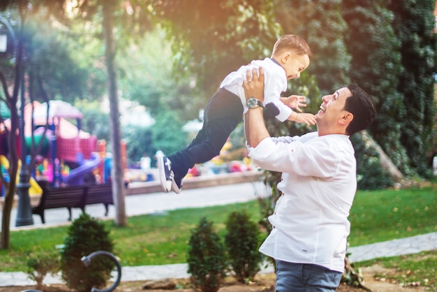 Weinig gelukkige jongen met zijn vader in de tuin. gelukkig familieconcept. Premium Foto
