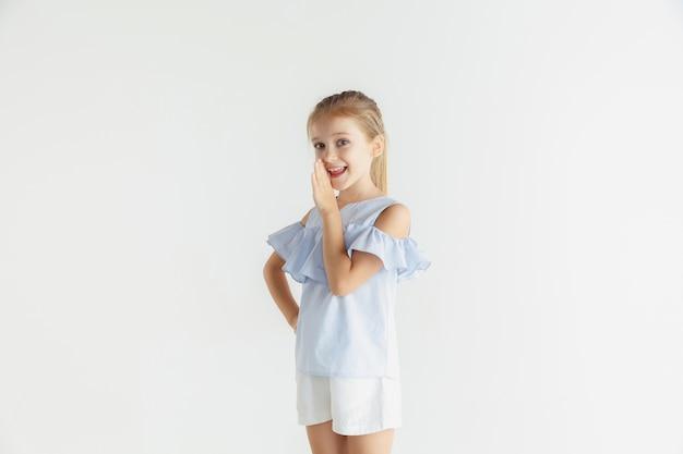 Weinig glimlachend meisje poseren in vrijetijdskleding op witte muur Gratis Foto