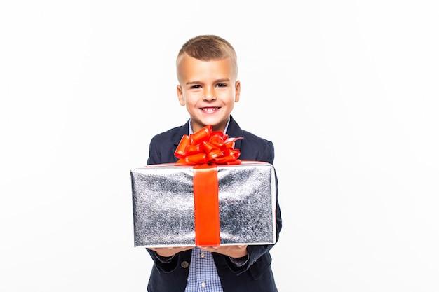 Weinig glimlachende jongen die huidige doos houdt die op witte muur wordt geïsoleerd Gratis Foto