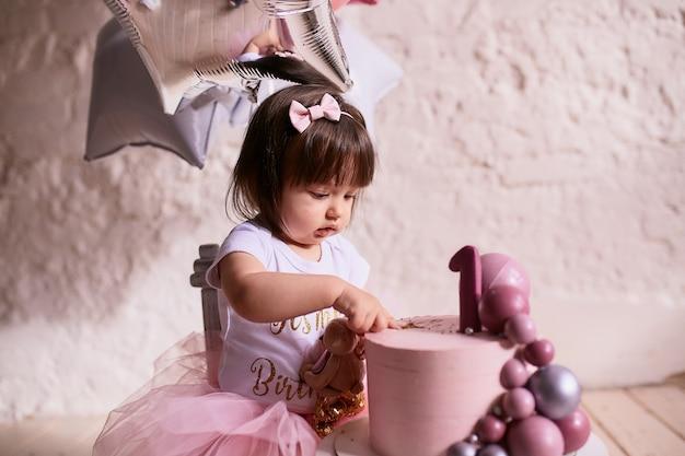 Weinig jarig meisje. charmante baby in roze jurk zit op de stoel Gratis Foto
