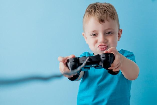 Weinig jong geitjejongen 2-3 jaar oud die blauwe kleren draagt houdt in handbedieningshendel voor portret van de gameson het blauwe achtergrond kinderenstudio. mensen jeugd levensstijl concept. bespotten kopie ruimte Premium Foto
