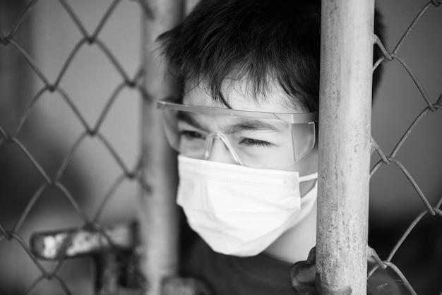 Weinig jongen blijft thuis quarantainetijd kijkend buiten uit het venster Premium Foto