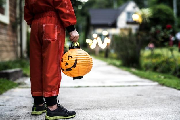 Weinig jongen die een halloween-lantaarn houdt Gratis Foto