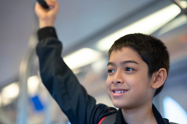 Weinig jongen die elektrisch kaartje koopt en in het openbare hemeltreinstation loopt met familie Premium Foto