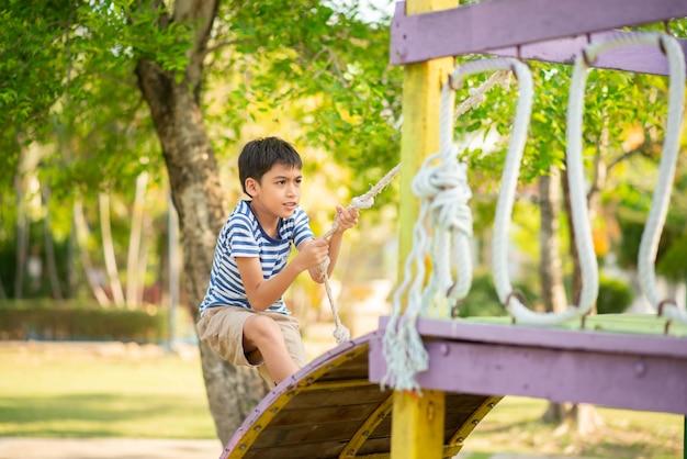 Weinig jongen die in de speelplaats openlucht speelt Premium Foto