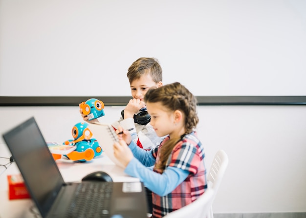 Weinig jongen die meisje bekijken die op notitieboekje met pen in het klaslokaal trekken Gratis Foto