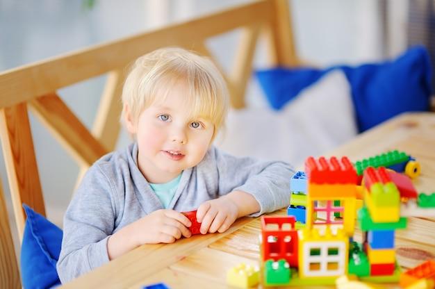 Weinig jongen die met kleurrijke plastic blokken bij kleuterschool speelt of thuis Premium Foto