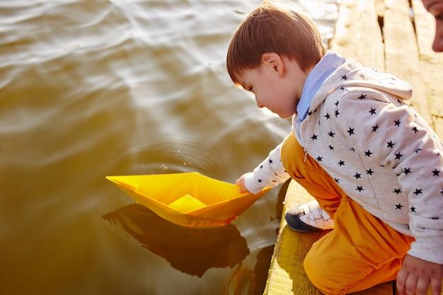 Weinig jongen die met stuk speelgoed document schip door het meer speelt Gratis Foto