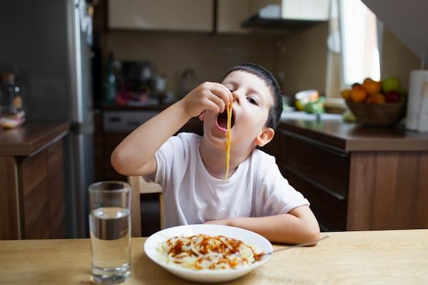 Weinig jongen die met zijn schotel van handendeegwaren eet Gratis Foto
