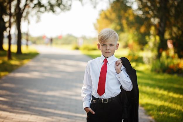 Weinig jongen die pak en rode band op aardachtergrond draagt Premium Foto