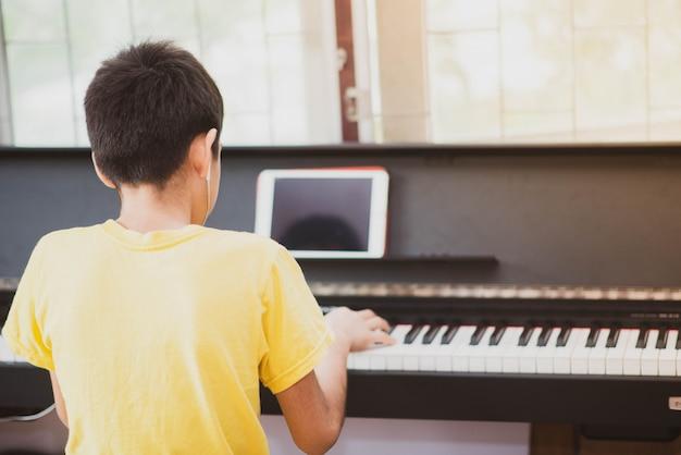 Weinig jongen die piano online digitale tablet thuis uitoefenen Premium Foto
