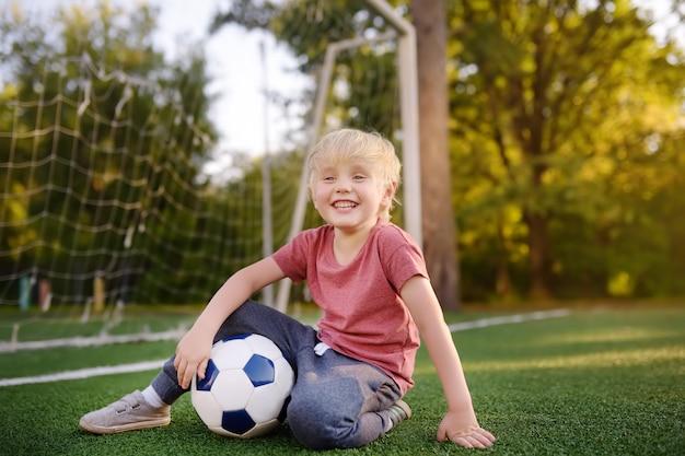 Weinig jongen die pret heeft die een voetbal / een voetbalspel op de zomerdag speelt. Premium Foto