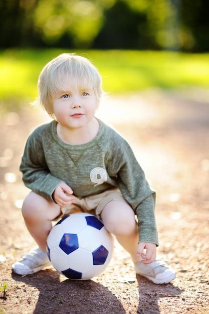 Weinig jongen die pret heeft die een voetbal / een voetbalspel op de zomerdag speelt Premium Foto