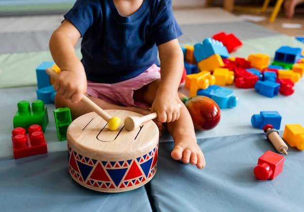 Weinig jongen die pret heeft en houten stuk speelgoed trommel speelt Premium Foto