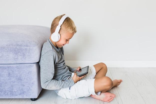 Weinig jongen die pret met tablet en oortelefoons heeft Gratis Foto