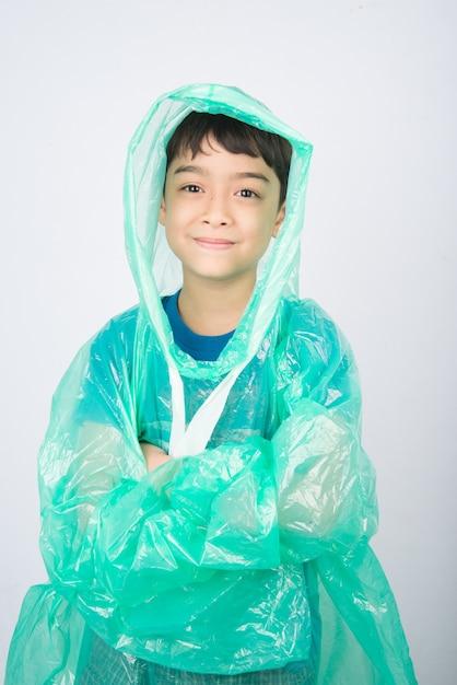 Weinig jongen die regenjas op witte muur draagt Premium Foto