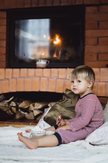 Weinig jongen door het vuur en warme chocolademelk met marshmallows Gratis Foto